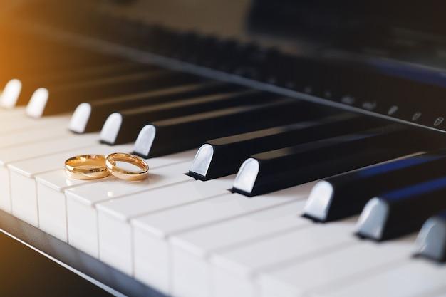 Les anneaux d'or de mariage se trouvent sur les touches du piano.