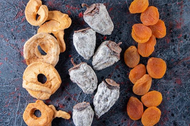Anneaux de pomme séchés, abricots et kakis savoureux sur une surface sombre.