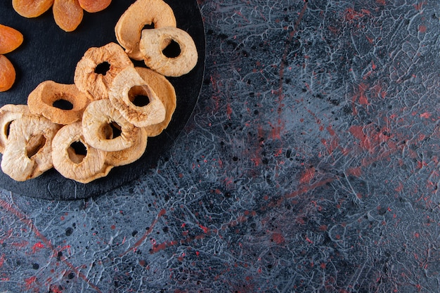 Anneaux de pomme séchés et abricots sur une planche à découper noire.