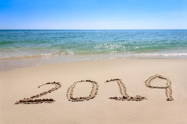Année 2019 écrite sur la plage de sable avec de l'eau de la mer