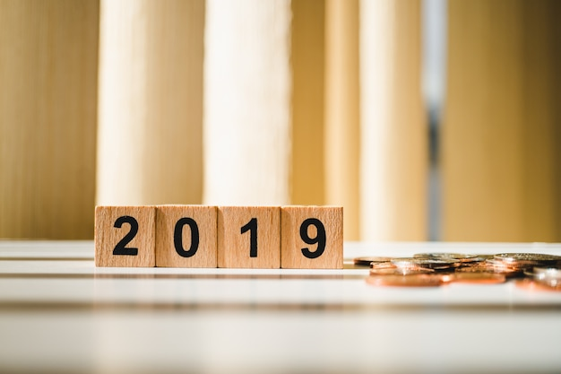 Année de bloc en bois 2019 avec des pièces de pile utilisant comme concept d'affaires et des finances