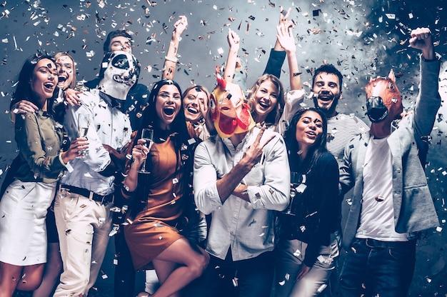 Année du coq. groupe de jeunes portant des masques d'animaux jetant des confettis et ayant l'air heureux