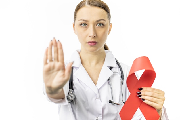 Années 30, femme médecin avec ruban rouge pour la sensibilisation au sida sur le mur blanc