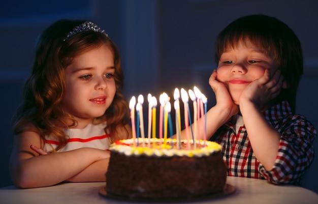 Anniversaire des enfants. enfants près d'un gâteau d'anniversaire avec des bougies.