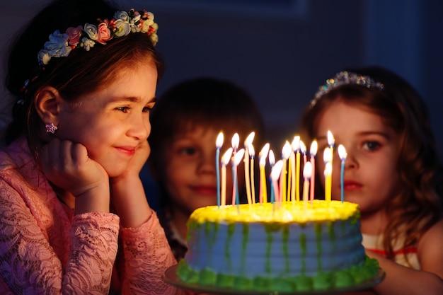 Anniversaire des enfants. enfants près d'un gâteau d'anniversaire avec bougies.