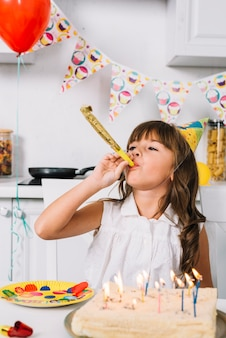 Anniversaire fille soufflant corne de parti assis derrière le gâteau d'anniversaire avec des bougies