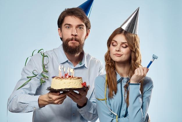 Anniversaire homme femme en chapeaux de fête sur un mur bleu et un gâteau avec des bougies.