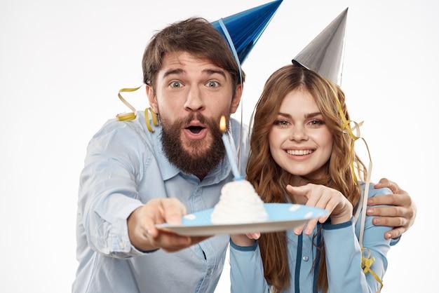 Anniversaire homme et femme avec un petit gâteau et une bougie dans un chapeau de fête, fond blanc