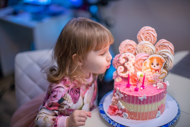 Anniversaire. une petite fille heureuse souffle les bougies sur le gâteau d'anniversaire.