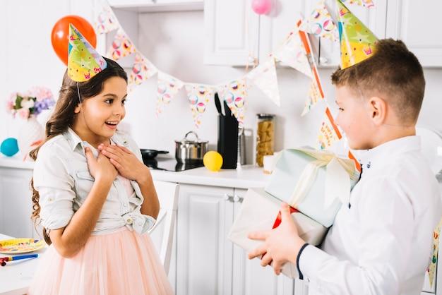 Anniversaire surprise fille regardant garçon portant des coffrets cadeaux à la main