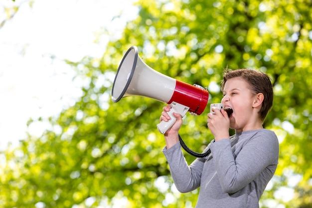 Annonçant le concept, garçon criant ou criant à travers le mégaphone sur la forêt
