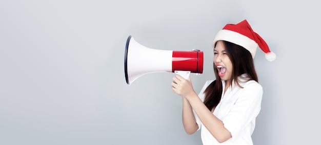 Annonce au client avec mégaphone avec salutation femme asiatique avec bonnet de noel
