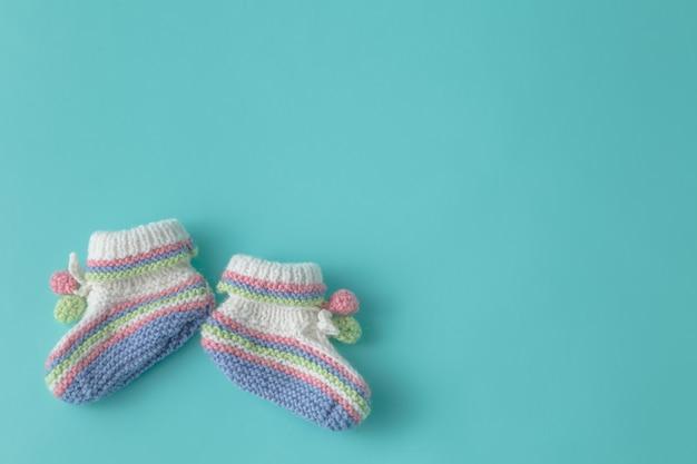 Annonce du nouveau-né. chaussons bébé tricotés sur fond uni aigue-marine