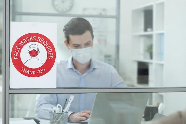 Annonce sur l'exigence de porter un masque de protection sur le mur de verre d'un bureau moderne avec un jeune homme d'affaires en réseau derrière