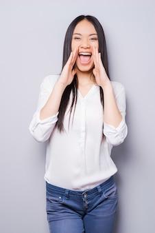 Annoncer la bonne nouvelle. jolie jeune femme asiatique criant et tenant la main près de la bouche en se tenant debout sur fond gris