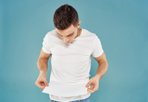 Annonceur masculin avec une feuille de papier blanc sur une maquette de fond bleu flyer. photo de haute qualité