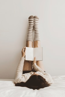 Anonyme femme lisant un livre près du mur