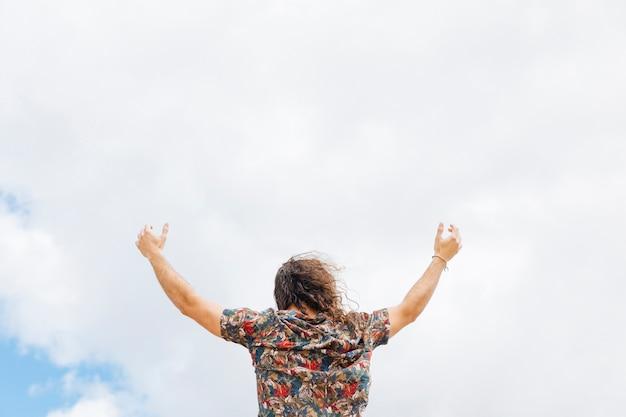 Anonyme mâle levant les mains vers ciel nuageux