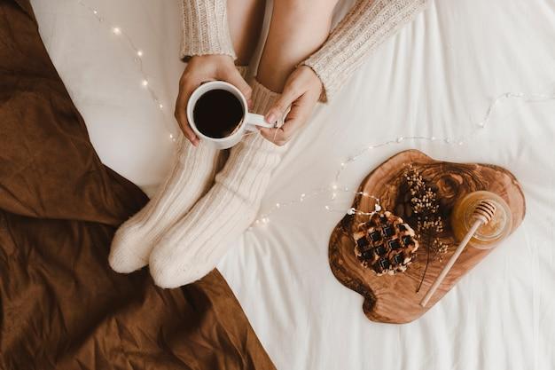 Anonyme avec thé près des desserts