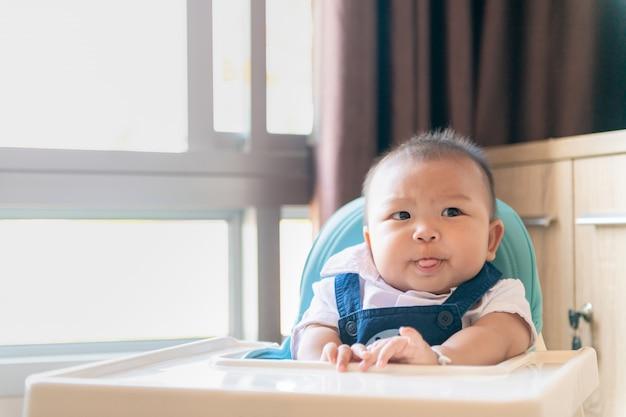 L'anorexie, bébé garçon assis sur une chaise d'alimentation avec l'expression de la nourriture de dégoût.