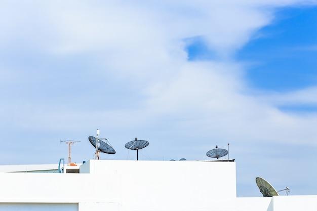 Antenne parabole au sommet du bâtiment en zone urbaine à midi