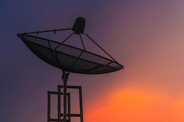 Antenne parabolique au crépuscule du ciel dans la ville