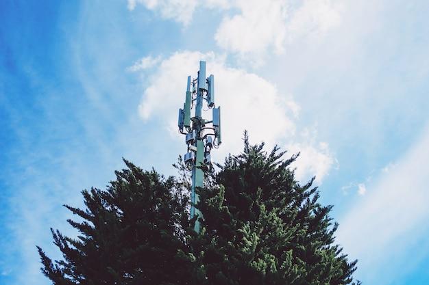Antenne de répéteur de communication de téléphone portable. tour de la cellule sur fond de ciel bleu