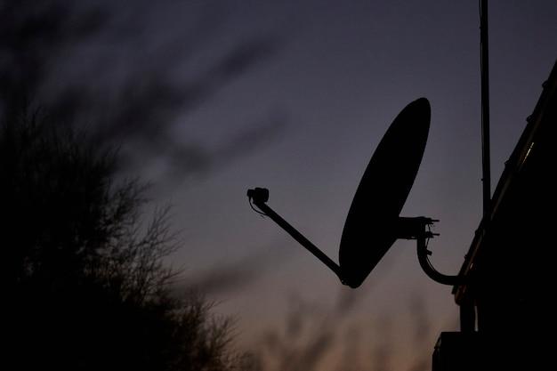 Antenne satellite dans la nuit au crépuscule
