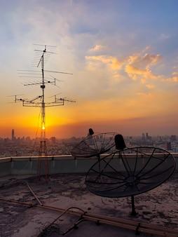 Antennes de télévision avec ciel crépusculaire en fond de paysage urbain.