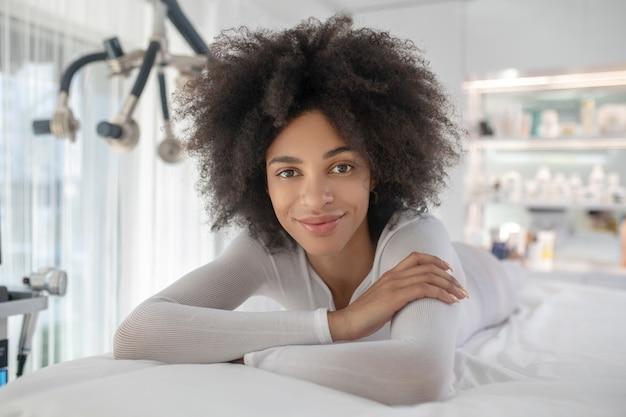 Anticipation agréable. jolie jeune fille aux cheveux bouclés reposant sur un canapé dans un salon de beauté dans une agréable anticipation