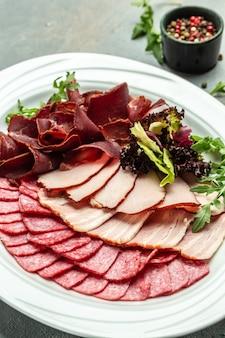 Antipasti au salami, prosciutto, jambon, assiette de viande avec sélection. image verticale. vue de dessus.