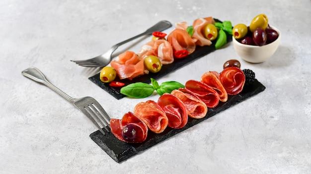 Antipasti dans un restaurant italien avec prosciutto et salami, olives, servis sur des plats en pierre noire.