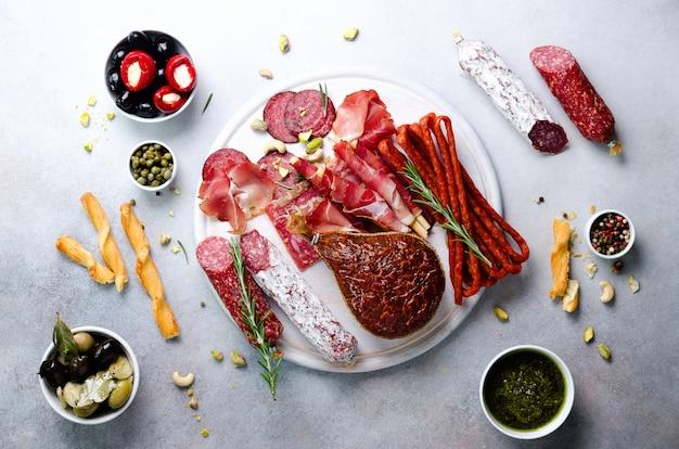Antipasti traditionnel italien, planche à découper avec salami, viande fumée à froid, prosciutto, jambon, fromage, olives, câpres sur fond gris.