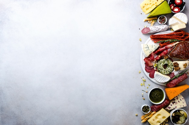 Antipasti traditionnel italien, planche à découper avec salami, viande fumée à froid, prosciutto, jambon, fromages, olives, câpres sur fond gris. apéritif au fromage et à la viande. vue de dessus, espace de copie, pose à plat