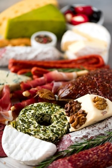 Antipasti traditionnel italien, planche à découper avec salami, viande fumée à froid, prosciutto, jambon, fromages, olives, câpres sur fond gris.