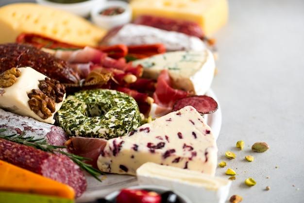 Antipasti traditionnel italien, planche à découper avec salami, viande fumée à froid, prosciutto, jambon, fromages, olives, câpres
