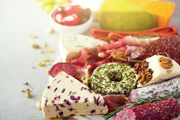 Antipasti traditionnel italien, planche à découper avec salami, viande fumée à froid, prosciutto