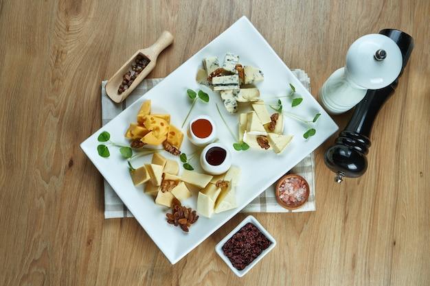 Antipasto - une assiette de fromages. différents fromages faits maison sur une plaque en céramique - brie, camembert, néerlandais avec du miel et des noix. apéritif au vin. nourriture vue de dessus