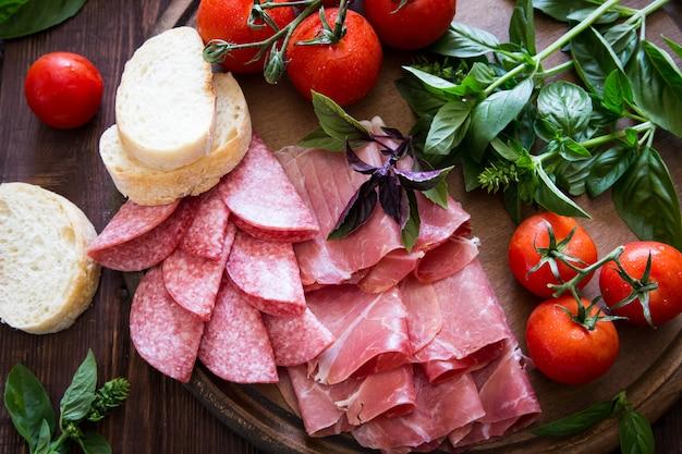 Antipasto au jambon, bresaola et salami. pain, tomate et basilic.