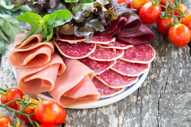 Antipasto au jambon, salami et bresaola. tomate et basilic. mise au point sélective