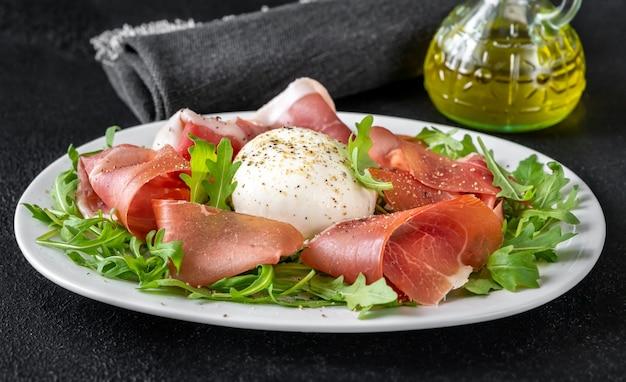 Antipasto au prosciutto, mozzarella et roquette fraîche sur l'assiette de service