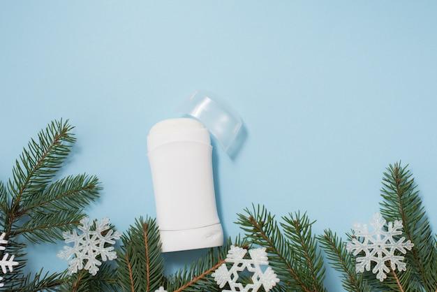 Antisudorifique ou déodorant blanc avec arbre de noël et flocons de neige sur fond bleu, copyspace
