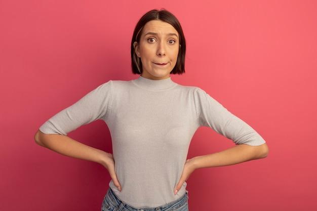 Anxieuse femme assez caucasienne met les mains sur la taille et regarde la caméra sur rose