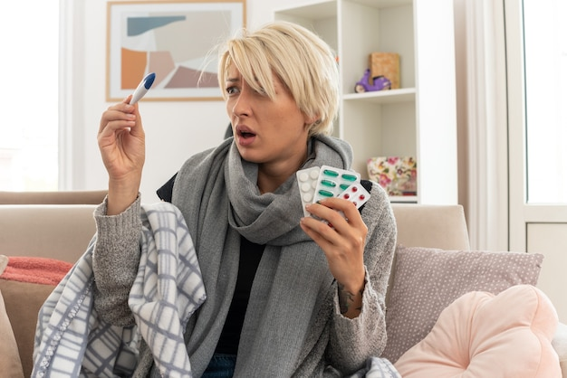 Anxieuse jeune femme slave malade avec une écharpe autour du cou enveloppée dans un plaid tenant des blisters de médicaments et regardant un thermomètre assis sur un canapé dans le salon