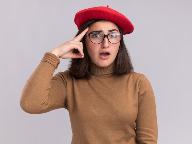 Anxieuse jeune fille assez caucasienne avec béret et lunettes optiques met le doigt sur la tempe sur blanc