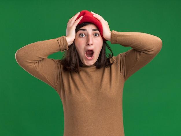 Anxieuse jeune fille assez caucasienne avec chapeau de béret met les mains sur la tête sur le vert