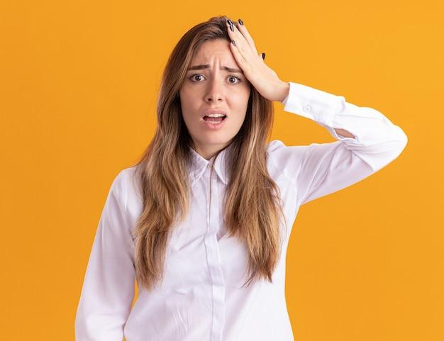 Anxieuse jeune fille assez caucasienne met la main sur le front et regarde la caméra sur orange