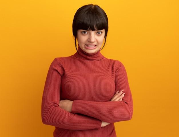Anxieuse jeune fille caucasienne brune se tient les bras croisés isolés sur un mur orange avec espace pour copie