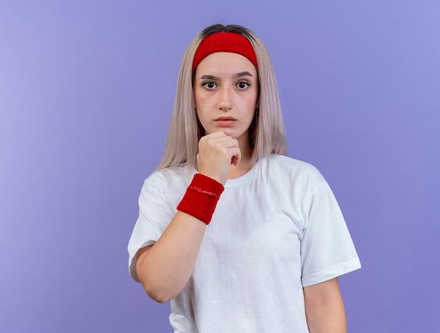 Anxieuse jeune fille sportive caucasienne avec des accolades portant bandeau
