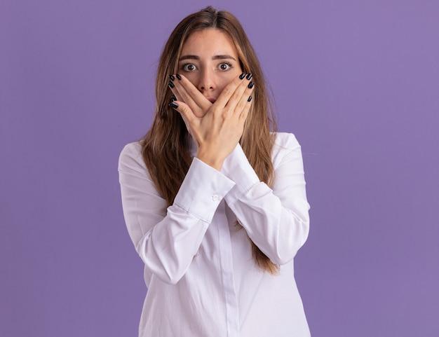Anxieuse jeune jolie fille caucasienne croise les mains et tient devant le visage isolé sur un mur violet avec espace de copie